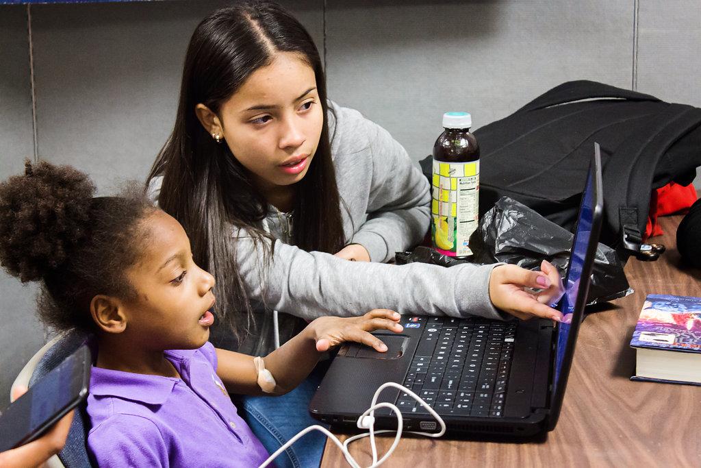 Kids use a computer together for homework